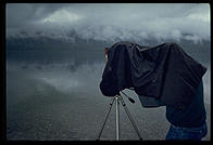 A dedicated view camera user works in a steady rain. Glacier National Park, Montana