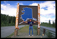 Philip at the Welcome to Alaska sign on the Alaska Highway, July 4, 1993.